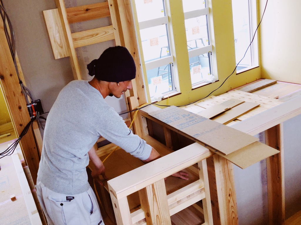 造作カウンターを養生している棟梁