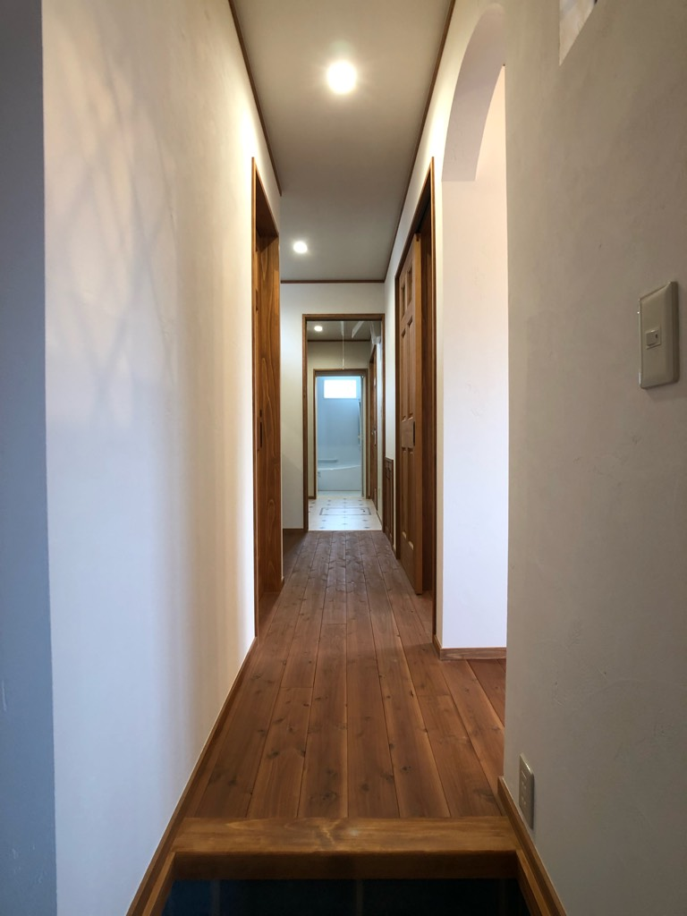 ファミリー玄関からトイレ洗面を横切って浴室、キッチンに抜ける廊下