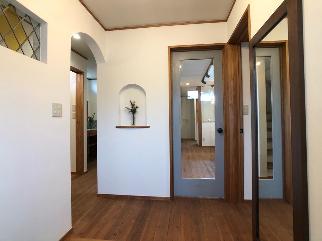 枠をブルーグレーに染めたガラスドアとニッチのある玄関ホール